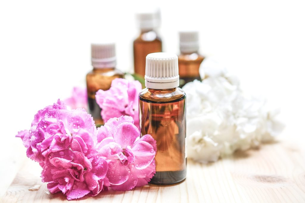 best essential oils for cellulite, oil bottles and flowers
