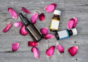best essential oils for cellulite, 3 essential oil bottles around petals