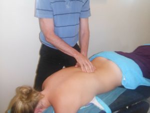 woman receiving massage treatment while lying face down