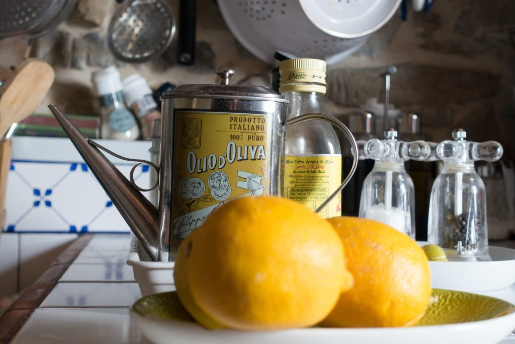 lemons on a plate next to bottle of oil