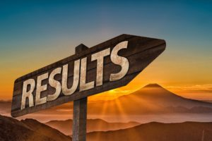 "sign above mountain landscape saying ""results"""