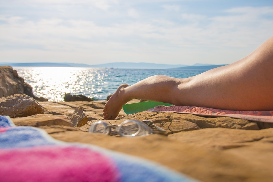 woman with smooth leg laying on a towel on beach