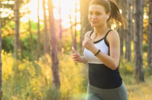 a woman jogging through the woods