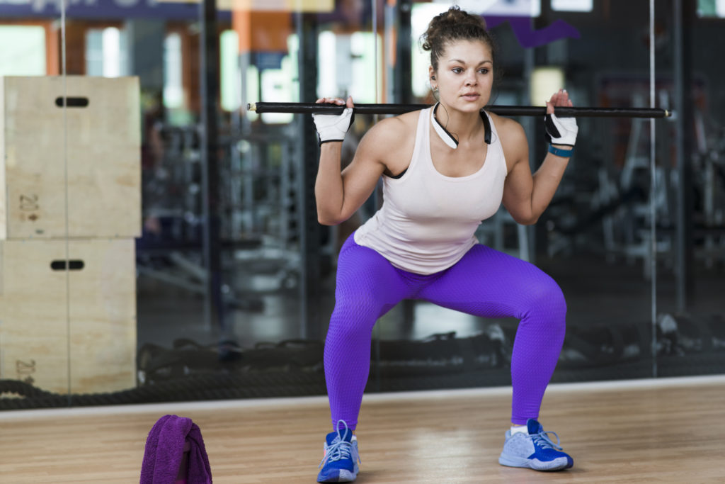 woman squatting with barbell