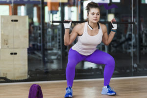 woman performing squats with barbell