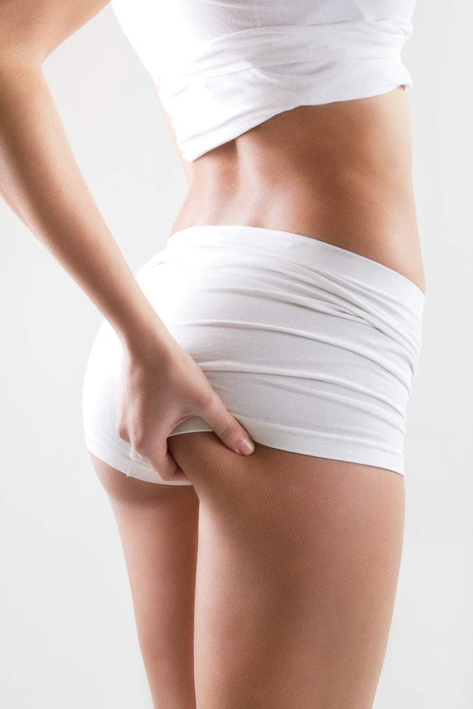 skinny with bad cellulite, woman pinching cellulite on buttock