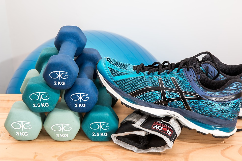 sneakers next to pile of dumbbells