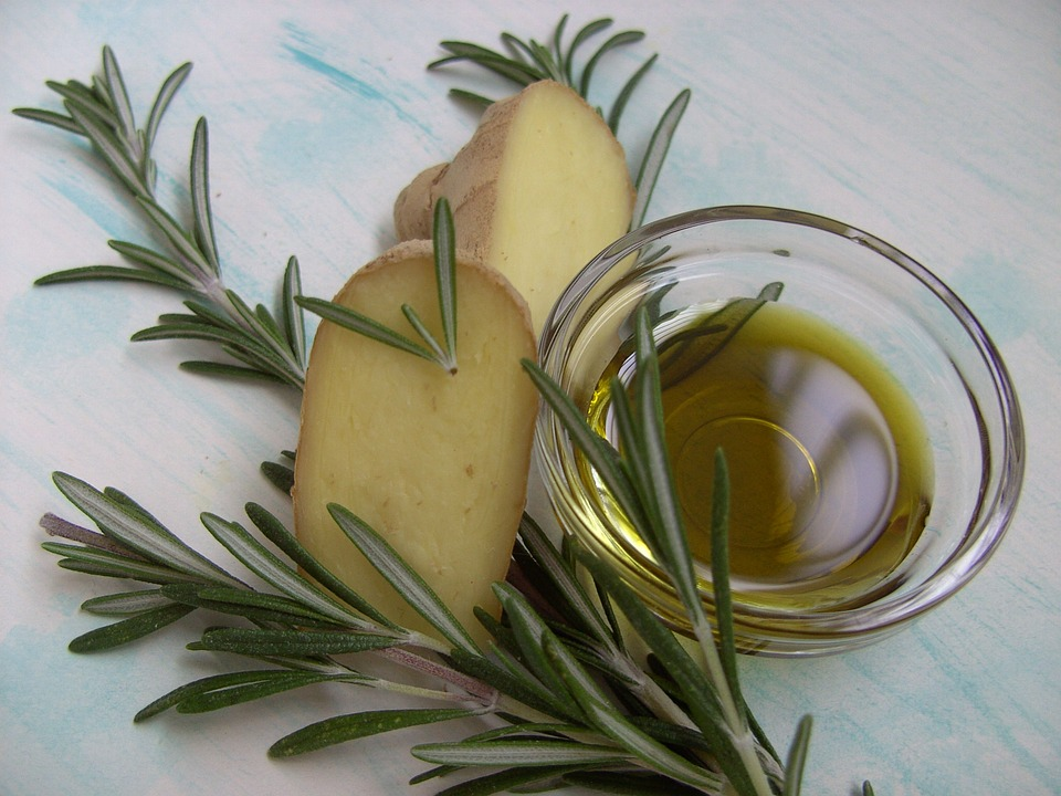branch of rosemary next to jar of rosemary oil