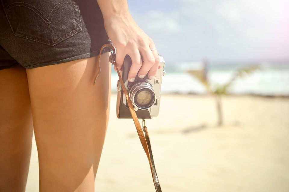 woman with slim smooth legs holding camera at beach