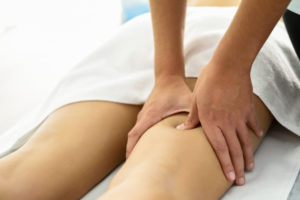 woman receiving massage on thigh