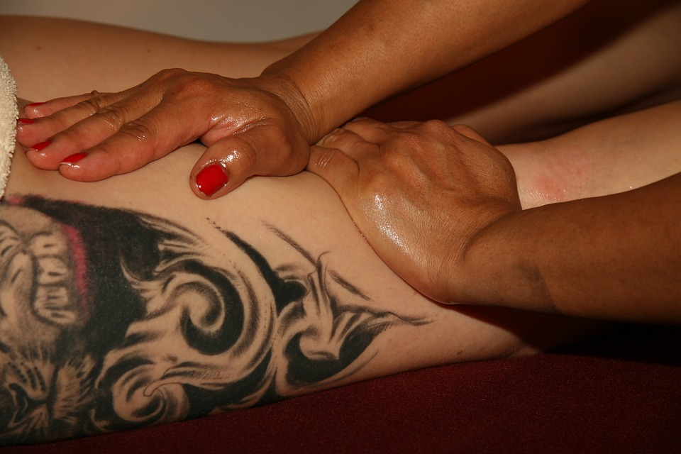 can tattoos hide cellulite, woman receiving massage on thigh with tattoo
