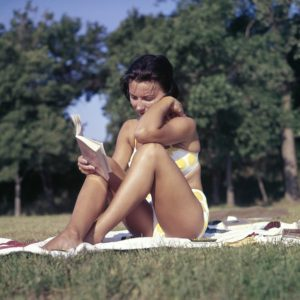 woman reading book while suntanning