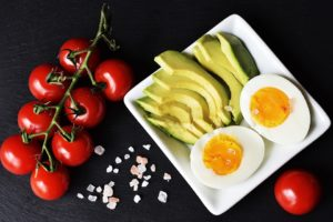keto diet foods berries, avocado and eggs on plate