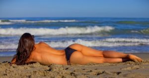 woman in bathers lying on side facing shore of beach